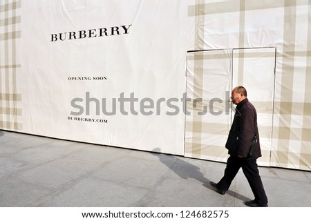 BEIJING - MARCH 11:Chines man walks besid a new Burberry shop on Mar 11 2009 in Beijing China.China is the second largest importer of goods in the world.
