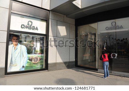 BEIJING - MARCH 11:Chines woman cleans new Omega watches shop on Mar 11 2009 in Beijing China.China is the second largest importer of goods in the world.