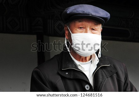 BEIJING-MARCH 15:Chinese man wear surgical masks on Mar 15 2009 in Beijing, China.In China it'?s common to wear masks if person is sick in courtesy to prevent spreading their own infection to others.