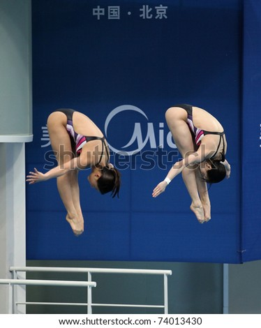 BEIJING - MARCH 25: He Zi and Wu Minxia of China perform during Women\'s 3m Springboard Synchro Final of the FINA/Midea Diving World Series 2011 on March 25, 2011 in Beijing, China.