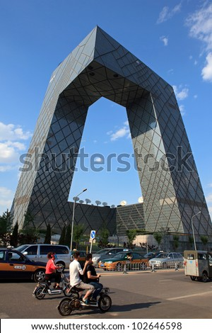 BEIJING-MAY 15: People cycle around China Central Television (CCTV) Headquarters, a 234 m and 44-storey skyscraper, on May 15, 2012 in Beijing downtown, China. CCTV is the National TV station of China