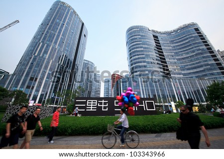 BEIJING-MAY 12: People walk and cycle around Sanlitun SOHO, a five shopping malls and nine office/apartment buildings designed by Japanese architect Kengo Kuma, on May 12, 2012 in Beijing, China.