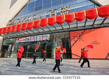 BEIJING - OCTOBER 14: Elderly women practice fan dance outside a shopping mall on October 14, 2012 in Beijing, China. Healthy living is promoted here as medical and healthcare cost escalates. - stock photo