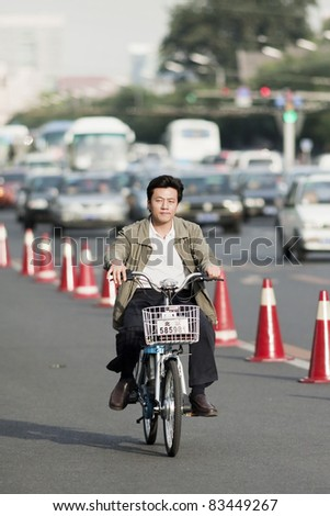 BEIJING  SEPT. 26. Man on electric bicycle in Beijing. Currently, many Beijing residents buy battery-powered bicycles to avoid wasting time on congested streets. Beijing on September 26, 2008.