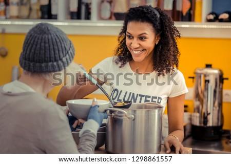Being a volunteer. Nice friendly woman smiling while enjoying her job as a volunteer