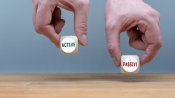 Being active or passive? Two Hands hold two dice with the words