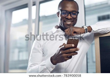 Being always in touch. Qualified young optimistic african man in glasses is reading emails using smartphone. He is expressing gladness while standing with gadget in office. Focus on hand with phone