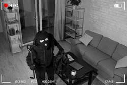 Being Caught. Robber entering house, holding crowbar and looking at CCTV camera, high angle view from above