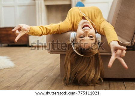 Being energetic. Pretty overjoyed young blond woman laughing and listening to music and wearing headphones while lying on the sofa and wearing a yellow sweater