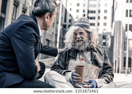 Being extremely kind. Smiling happy long-haired homeless man taking money from kind businessman while he sitting in front of him
