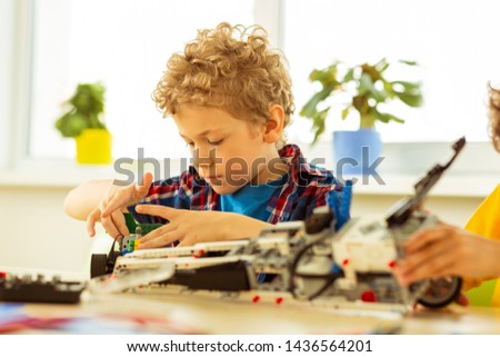 Being focused. Cute blonde boy concentrating on his task while constructing a car model