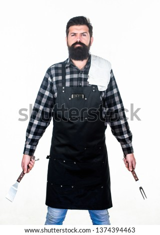 Being ready for bbq party. Grill cook holding spatula and bbq fork. Bearded man with bbq tools in hands. Happy hipster using stainless steel tools for preparing bbq food.