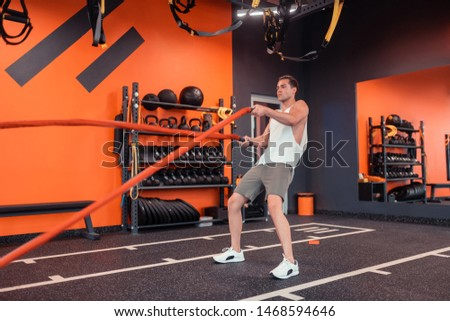 Being strong. Handsome strong man developing his strength while exercising with special ropes #1468594646