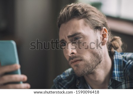 Being worried. Worried young handsome man looking at his smartphone