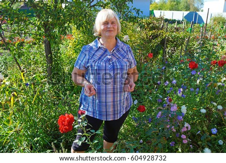 Belarus, Bobruisk District, September 22, 2015: A woman stands in the shade in her beautiful garden #604928732