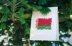 Belarus flag printed on a Christmas shopping bag. Close up of a shopping bag as a decoration on a Xmas tree on a street. New Year or Christmas shopping, local market sale and deals concept.