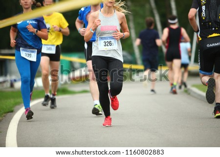 Belarus, Minsk, 22 July 2018: athletes, participants run to the finish during a triathlon competition in Minsk #1160802883