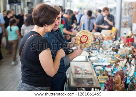 Belarusians  man and woman aged consider things in flea market #1281061465