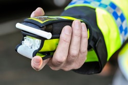 Belfast, Northern Ireland. 24 Nov 2016 - A police officer holds a roadside breathalyser alcohol breath test after taking a sample from a driver.