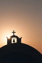 Belfry and christian cross on the dome of a church at sunset. Santorini cyclades island greece