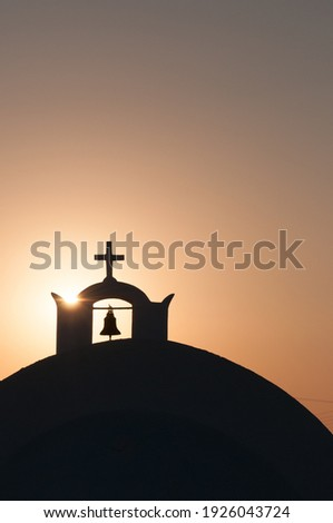 Belfry and christian cross on the dome of a church at sunset. Santorini cyclades island greece Stock photo ©