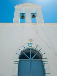 Belfry two bells small whitewashed chapel door with arch Kimolos island Cyclades Greece. Under view of traditional orthodox church blue sky background. Summer vacation religious destination. Vertical