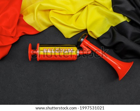 Belgian flag and soccer fan trumpet lie on a black background with space for text from below, top view close-up. Photo stock ©