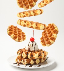 Belgian Liege Waffles With Ice Cream Ball And Chocolate Sauce, Cherry On Top And Levitation Waffles Around Plate Isolated On White Background. Side View.