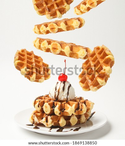 Belgian Liege Waffles With Ice Cream Ball And Chocolate Sauce, Cherry On Top And Levitation Waffles Around Plate Isolated On White Background. Side View. Stockfoto ©