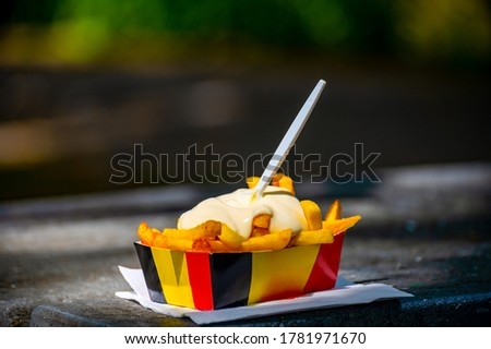 Belgian street and fast food, paper box in colors of Belgian flag with fried potato frit chips and mayonnaise sauсe. Photo stock ©