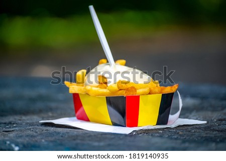 Belgian street and fast food, paper box in colors of Belgian flag with fried potato frit chips and mayonnaise sauсe. Сток-фото ©