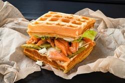 Belgian waffle with salmon on wood table. Keto Breakfast variation.
