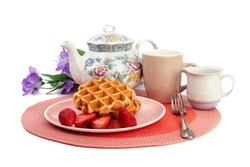 Belgian waffles with strawberries and whipped cream and a tea pot isolated on white