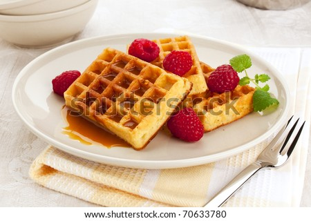 belgian waffles with syrup or caramel sauce served on a plate, garnished with raspberries and mint