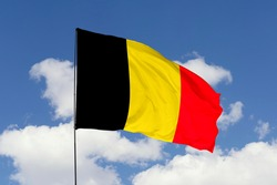 Belgium flag isolated on the blue sky with clipping path. close up waving flag of Belgium. flag symbols of Belgium.