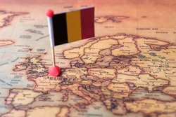 Belgium marked with a flag on the map. Flag of Belgium on the world map. The concept of travel and tourism.