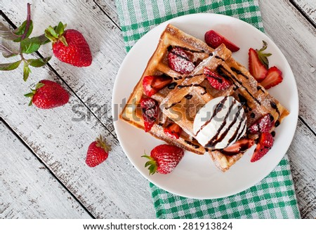 Belgium waffles with strawberries and ice cream  on white plate. Top view