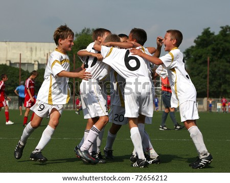 BELGOROD, RUSSIA - AUGUST 04: Unidentified boys embraces after goal on August, 04 2010 in Belgorod, Russia. The final of Chernozemje superiority, Football kinder team of 1996 year of birth.