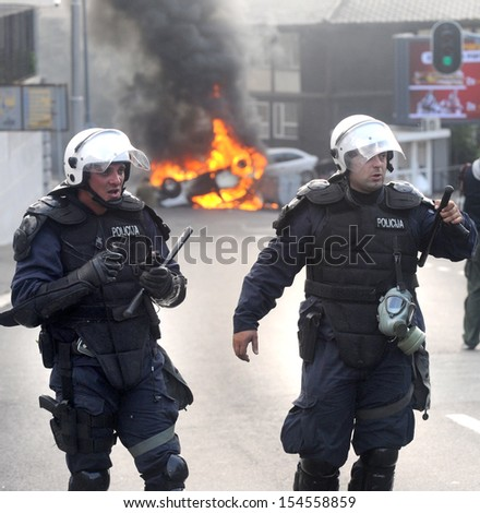 """BELGRADE, SERBIA - CIRCA OCTOBER 2010: Special force policeman watches burning police car after riots at """"Belgrade Pride"""" circa October 2010 in Belgrade"""