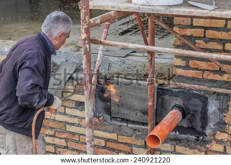 BELGRADE, SERBIA - DECEMBER 26: Pipe through the basement wall, outside coated with tar and patched. Basement seal around the waste pipe. At construction site in December 2014.