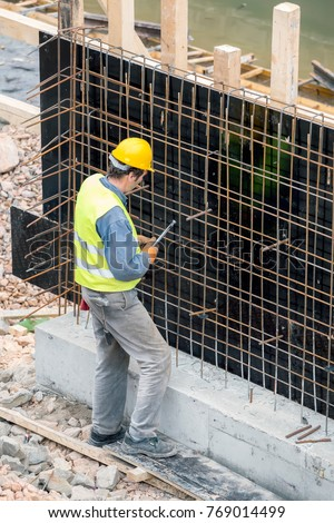 BELGRADE, SERBIA - FEBRUARY 24, 2017: Worker working on the retaining wall, tying rebar and reinforcement bar at the construction site.