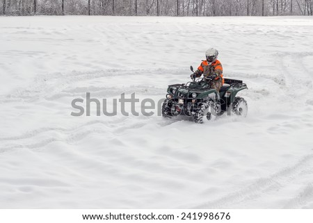 BELGRADE, SERBIA - JANUARY 06: Extreme winter sports, boy driving atv vehicle at winter. Snow Sport on 4 wheeled motor ATV.  All terrain vehicle in motion at winter on January 2015.