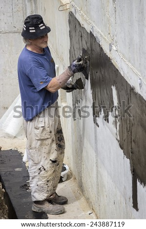 BELGRADE, SERBIA - MAY 24: Basement wall waterproofing,worker installing waterproofing tar sealer.Worker painting basement concrete wall with tar insulation material. At construction site in May 2014.