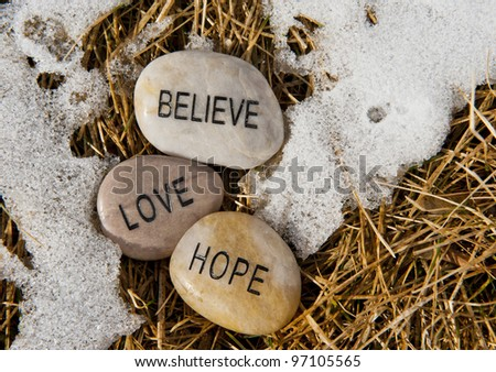 Believe, hope and love rock in the melting snow