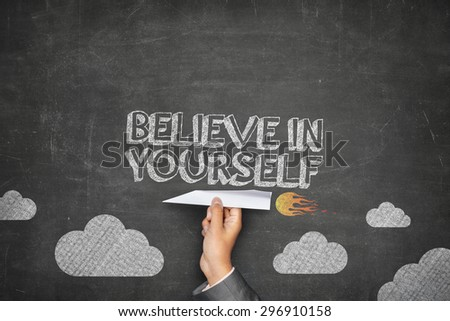 Believe in yourself concept on black blackboard with businessman hand holding paper plane