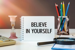 Believe in yourself is written on a notepad on an office desk with office accessories.