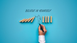 Believe in yourself sign over a hand drawn man stopping falling dominos in a conceptual image. Over blue background.