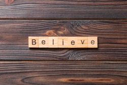 believe word written on wood block. believe text on table, concept.