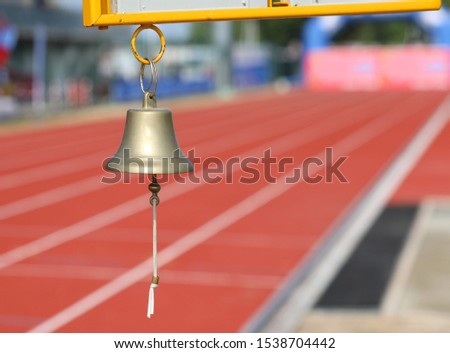 bell at the side of an athletics track to indicate to the athletes the last lap of the race