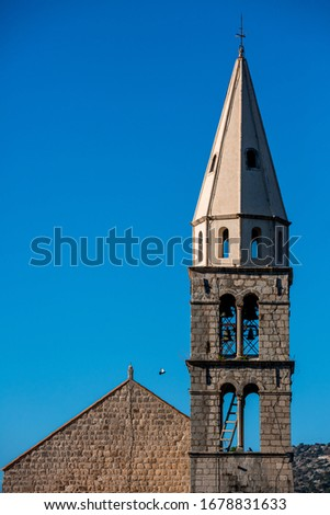 Bell cote tower of an old catholic church with gothic chapel, light blue sky on background, bird flying near the tower